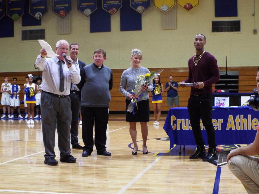 Alumni Travis Rudolph is welcomed and honored by Cardinal Newmans Father Carr, Dr. Higgins and Jay Lower.